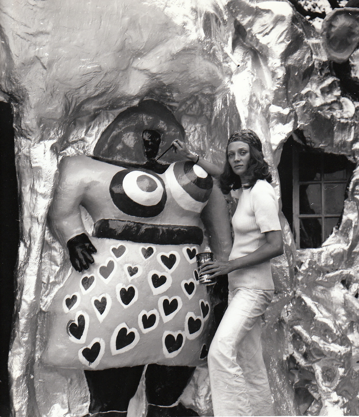Niki de Saint Phalle looks into the camera as she paints the Nana figure attached to Reve de L'Oiseau. The artist wears a head scarf, white sweater and pants.