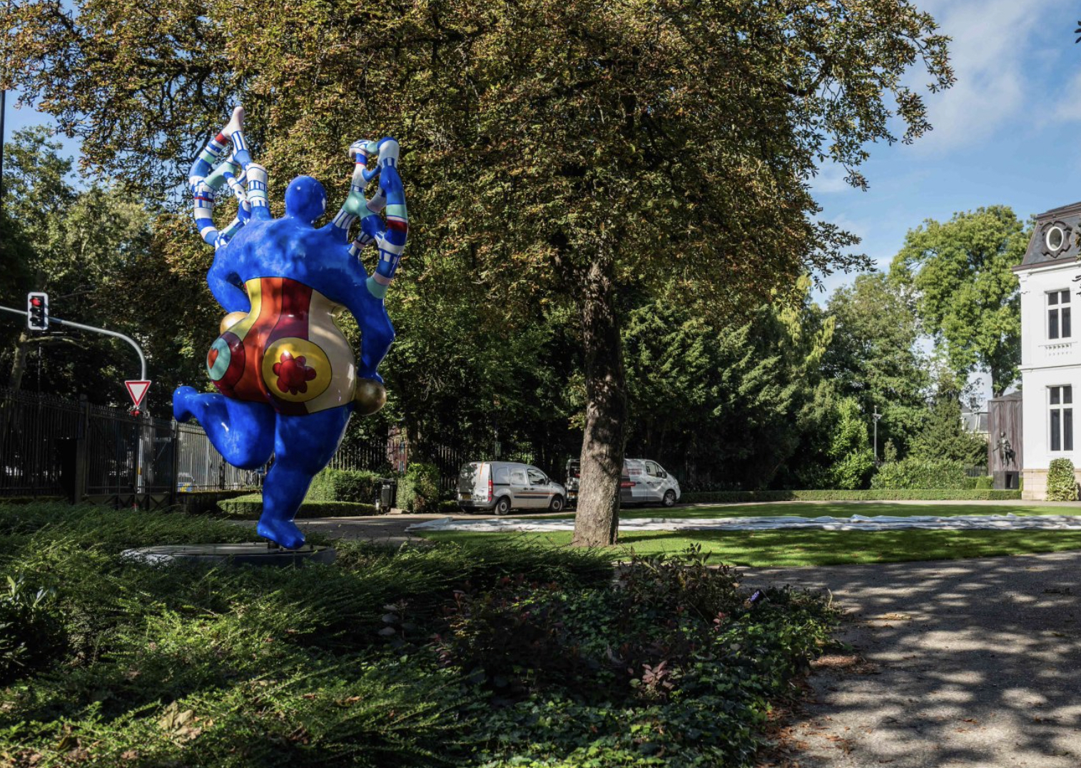 colorful painted polyester sculpture by Niki DE Saint Phalle in the shape of an angel installed in a lush green garden at Villa Vauban in Luxembourg